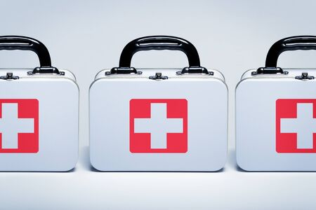 Be prepared, a row of tin first aid kit with cross emblem on grey background