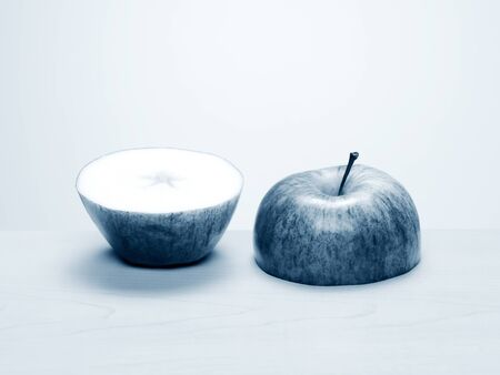 Two halves of a cut apple side by side on wood table. Black and white