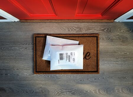 Envelope packages delivered to door step. Overhead view.