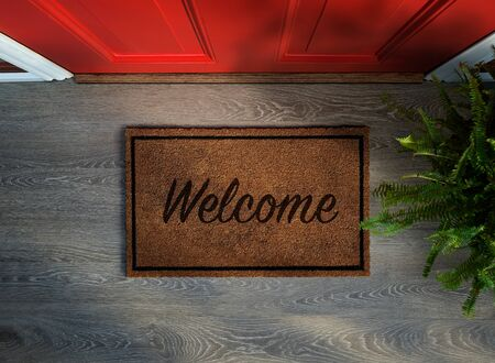 Overhead view of welcome mat outside inviting front door of house with potted fern plant