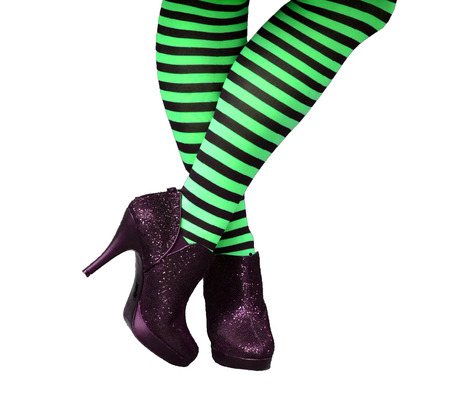 stockings feet: Female legs and feet in green and black striped stockings and sparkly black high heels Stock Photo