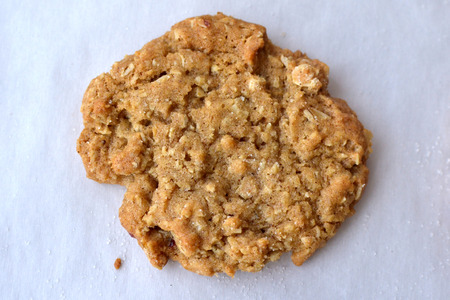 dusting: Single golden brown oatmeal cookie on white parchment paper with dusting of sugar Stock Photo