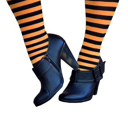 stockings feet: Legs and feet of witch with orange and black striped stockings with black heeled shoes Stock Photo