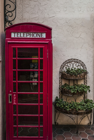 An old telephone booth and a planter. Stock fotó