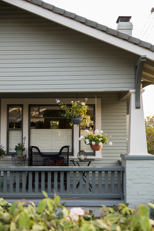 A vignette detail of two hanging potted plants on the front porch of a Craftsman style home. Banque d'images - 92527970