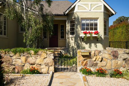 California home with entry iron gate and sandstone garden wall