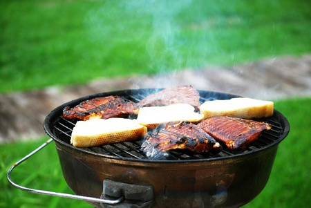 bar b que: -- Meat and bread cooking on a charcoal grill