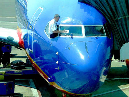Like a service station attendant, a jet pilot leans out the cockpit window of his aircraft to clean the windshield at the Boise Airport in Idaho.of his aircraft Редакционное
