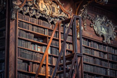 vecchi libri sulla mensola di legno in Biblioteca Nazionale Austriaca, Wien