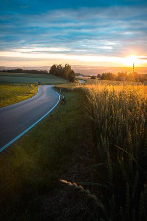 Zachód słońca drogowego miasta w polu, słońce, wieczorem