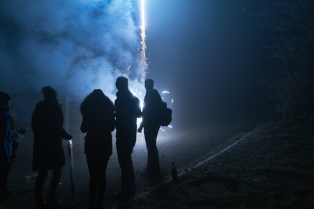 people standing and watching fireworks, silvester, dark, silhouette Stockfoto