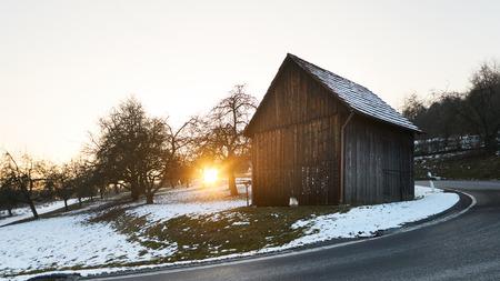 Holzkabine im Sonnenuntergang, Winter mit dunkler Straße in der Front der Ansicht, Schnee