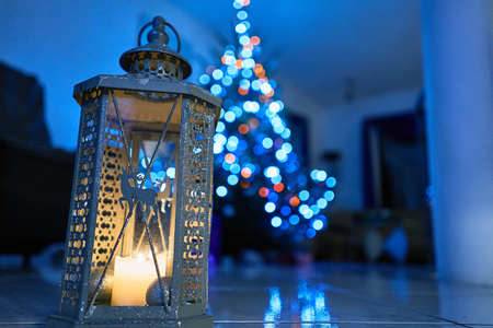 Christmas Lantern with decorations on marble floor. Christmas Tree in background, night and blue
