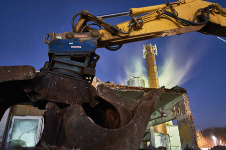 dumptruck: Excavator on stones at night, dark and blue