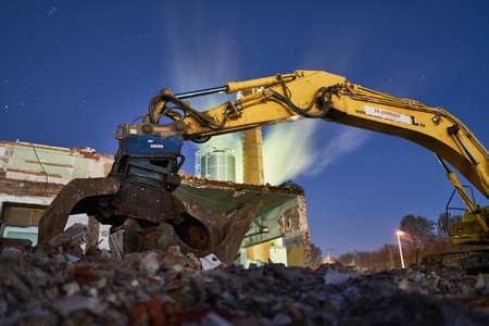 Excavator on stones at night, dark and blue