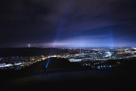 zaklamp schijnt in de lucht op de heuvel nabij Stuttgart Rotenberg tijdens de nacht, wolken