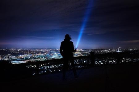 Die Taschenlampe glänzt bis zum Himmel auf einem Hügel bei Stuttgart Rotenberg in der Nacht, Wolken