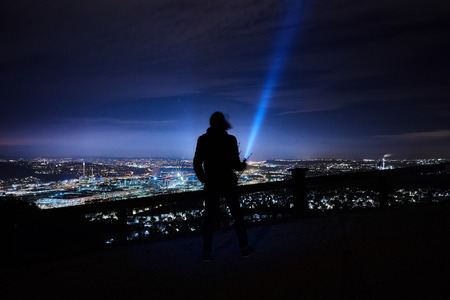 flashlight is shining up to the sky on a hill near Stuttgart Rotenberg during the night, clouds