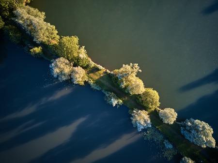 Top Blick auf einen kleinen See und grüne Bäume herum mit einem kleinen Pfad oder Straße