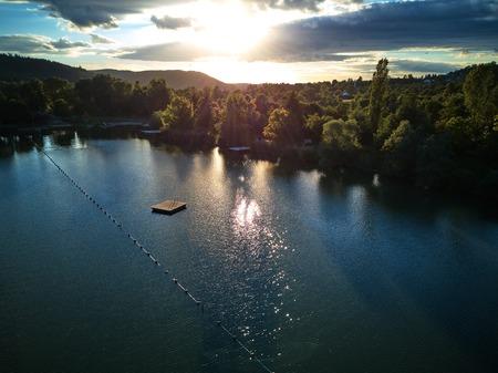 Widok na małe jezioro i zielone drzewa wokół o zachodzie słońca