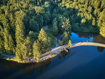 Bovenaanzicht van een klein meer en groene bomen rond met een klein pad of straat