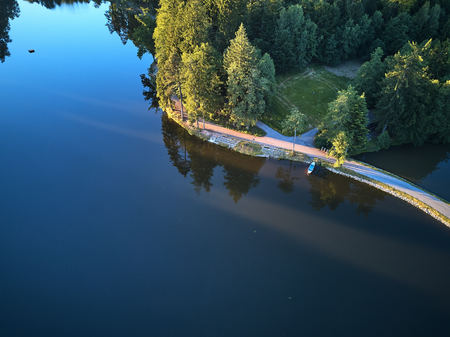 Widok z góry na małe jezioro i zielone drzewa wokół małej ścieżki lub ulicy Zdjęcie Seryjne