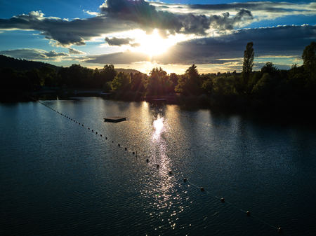 Zicht op een klein meer en groene bomen rond bij zonsondergang