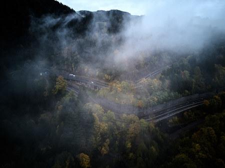 Straße von oben durch einen nebligen Wald im Herbst, Luftbild fliegt durch die Wolken mit Nebel und Bäumen