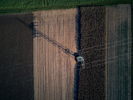 Drone flight aerial bird eye view of tractor mowing grass on beautiful green field and blue sky background farmer working with modern equipment moving over fresh grassland cutting grass for harvest
