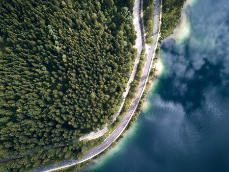 Aerial view of the road near the lake and the forest from above Standard-Bild