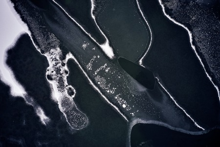 Aerial view of the winter frozen lake from above captured with a drone in Germany. Structure and Texture on the water.