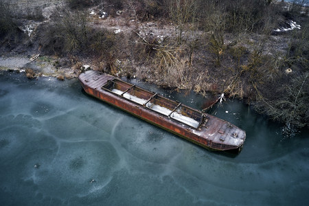 Old boat ship, trapped, frozen in winter ice lake, docked in pier, aerial top down view