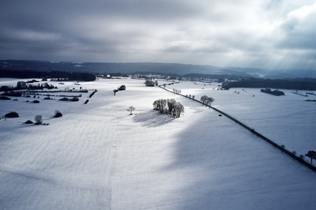 Aerial view of a winter curved road covered with snow. A snowy plateau with single trees captured from above with a drone. 写真素材