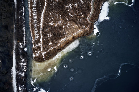 Aerial view of a frozen lake, water, brown grass and mud forming abstract image of natural textures. Shoot from drone in winter time