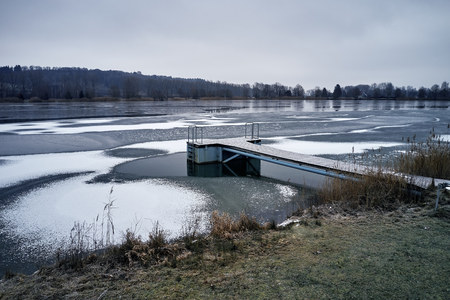 wooden pier on frozen lake on winter, snow and brown grass