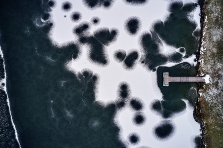 Aerial view of the winter frozen lake with wooden piers from above captured with a drone in Germany.