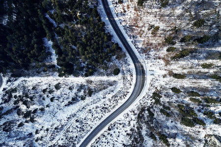 curved road in winter mountain landscape. Aerial view of forest and trees with a winding street surrounded by snow. 写真素材