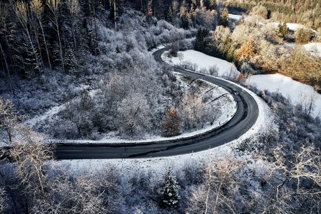 curved road in winter mountain landscape. Aerial view of forest and trees with a winding street surrounded by snow. Stockfoto