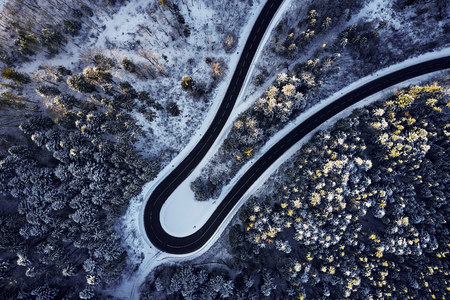 Aerial drone view of a curved winding road through the forest high up in the mountains in the winter with snow covered trees and curved streets in winter