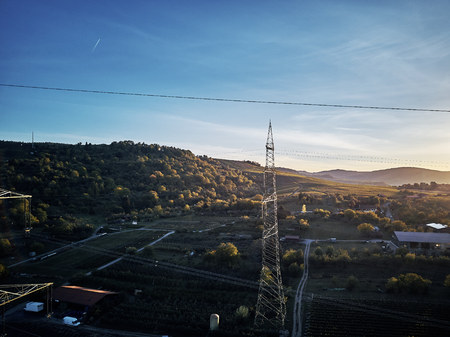 Aerial view of power line pylon near town in the fields on sunset. Orange Teal warm autumn setting