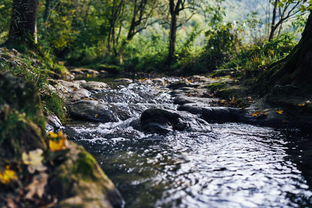 A river creek with a small waterfall. Sunset and strong detail bokeh view. blue calm warm water