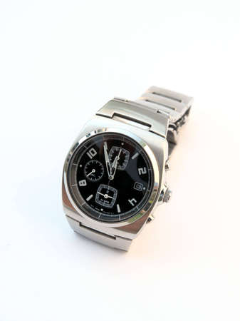 A metallic watch with black clock face on white background photo