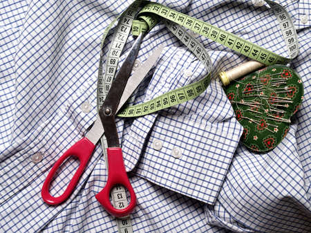 sewing supplies:  The image shows a part of a shirt with some sewing supplies Stock Photo