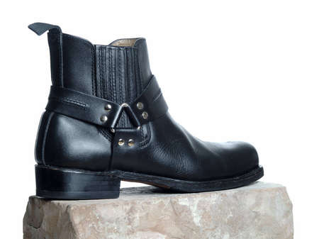 bootee: The picture shows a black bootee on a brick