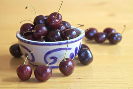 The image shows a cup filled with cherries