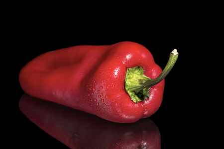 ingradient: The image shows a red pepper over reflective black background