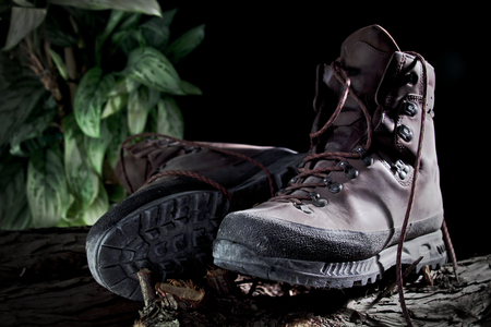 hiking boots: The image shows used hiking boots on wooden boards