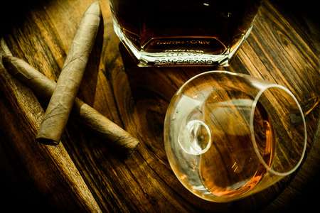 Top view of two cigars, a glass and a bottle of rum on a wooden surface
