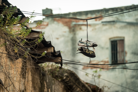 Old worn out shoes tossed on a wire (shoefitti) in from of a old building or ruin