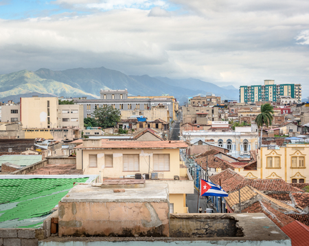 Cuban flag waving in Santiago de Cuba with the city and mountains in the back